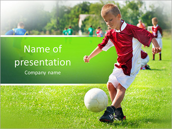 Boy kicking football on the sports field PowerPoint Template