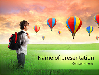 Child carrying a backpack standing on a green meadow with hot-air balloons in the background PowerPoint Template