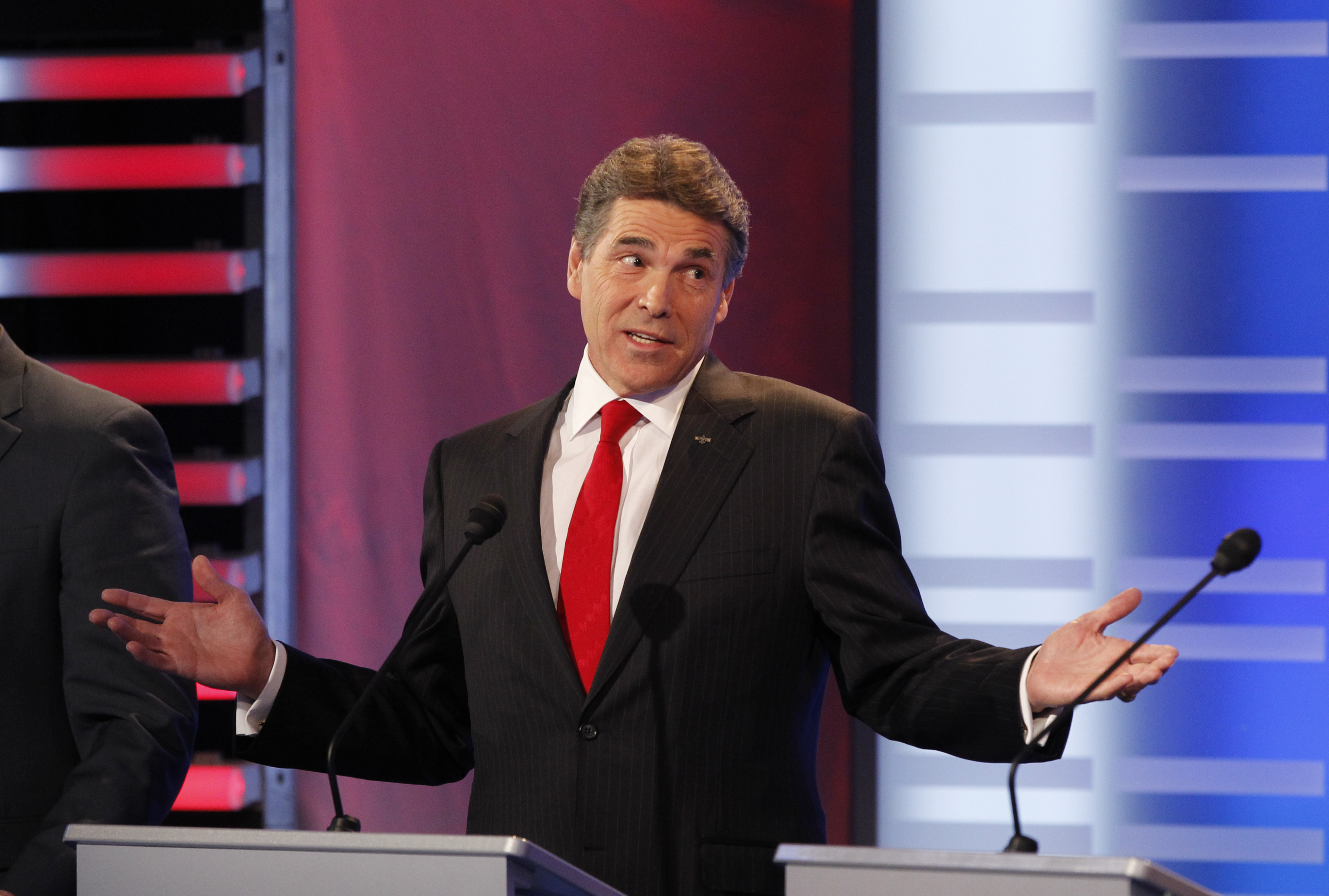 Rick Perry gestures with his hands at a podium
