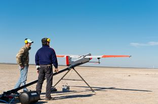 Texas A&M University-Corpus Christi engineering student Adam Ersepke and lab coordinator Jack Edward Esparza prepare for the take off of  the University's RS-16 unmanned aerial vehicle, otherwise known as a drone, for a test flight over the Kennedy Ranch near Sarita, Texas on January 18, 2013.