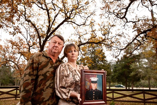 Dennis and Patty Thuesen hold a photo of their son John Thuesen on Dec. 11, 2013. An Iraq war veteran, John Thuesen is appealing his death row sentence for the murders of his girlfriend and her brother, arguing that jurors at his trial were not adequately informed about post-traumatic stress disorder.