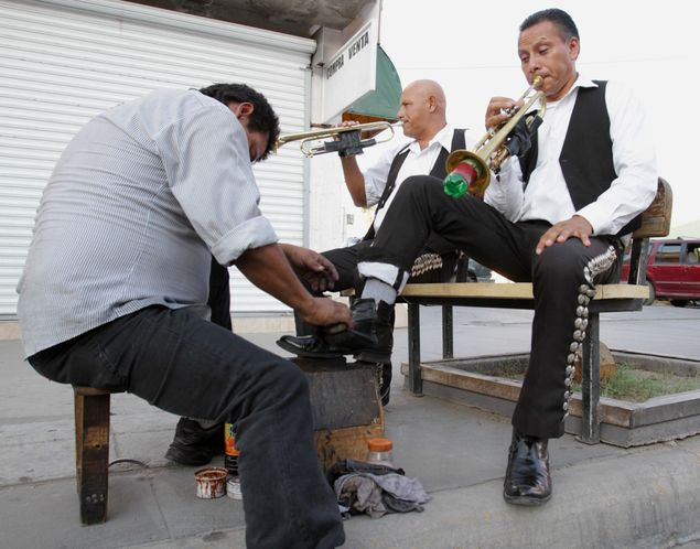 Ignacio Villa, left, and Arturo Ibarra, right, of the mariachi group Los Gavilanes get their shoes shined on Avenida Juárez in Ciudad Juárez, México, on Jul. 9, 2013.