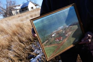 Mike Skinner holds a decades-old aerial photograph of the land near Spearman that three generations of his family had farmed.