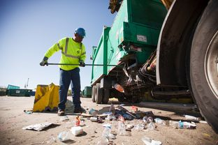 Glenn Bailey cleans out a city of Houston recycling truck on March 18.