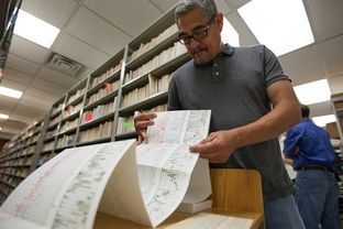 Daniel Ortuño, who manages the 1.5 million drilling records stored at the University of Texas at Austin's Bureau of Economic Geology, unfurls a drilling log. State water researchers are using information on some logs to map potential water sources.
