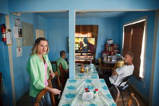 Checking in on residents in the dining area, Shiela Jarboe Lickteig, the owner The Hand Up, Inc halfway house in Houston Monday, June 2, 2014 is dealing with the death of her husband who died  last month who ran the place with her.
