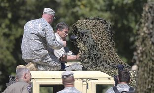 Gov. Rick Perry views Humvee-mounted high-tech optical equipment as he tours Camp Swift National Guard training on Aug. 13, 2014.