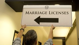 Frank Roberts of the Travis County Clerk's office hangs a sign directing couples to the clerk's office on June 26, 2015.