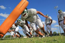 In Brownsville, offensive linemen for Pace High School's football team hit a sled during a Sept. 11 practice.