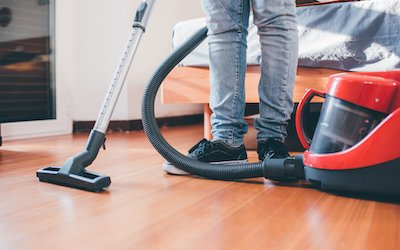 Person vacuuming hardwood floors with canister vacuum