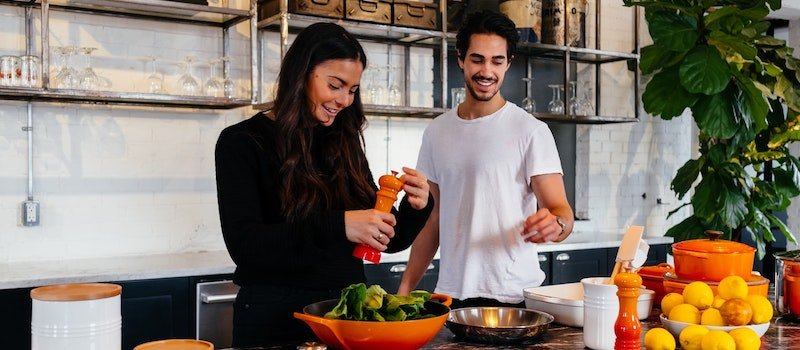 Man and woman in kitchen cooking with vegetables and citrus