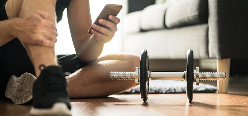 Man uses phone while next to workout equipment in living room
