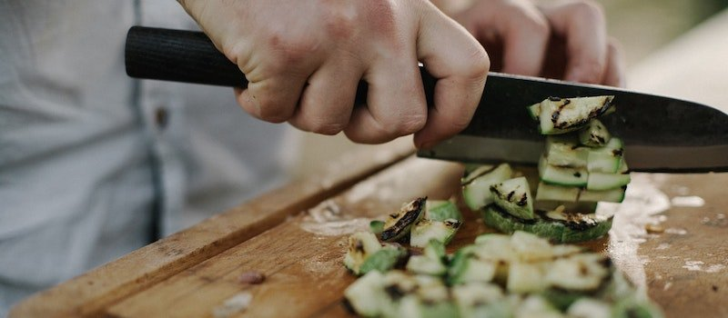 Person cutting vegetables on cutting board