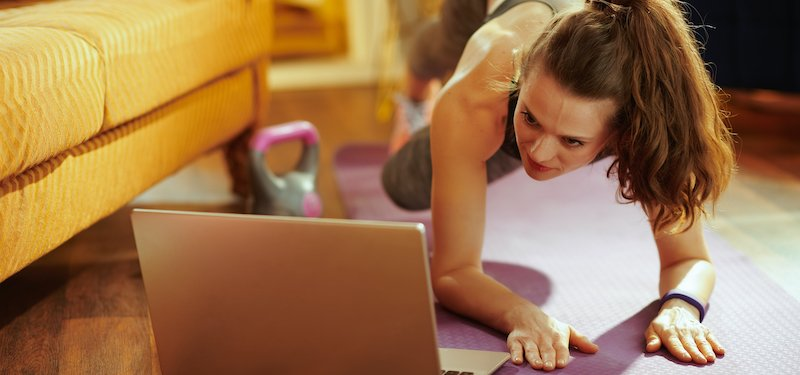 Woman works out on yoga mat in front of a computer