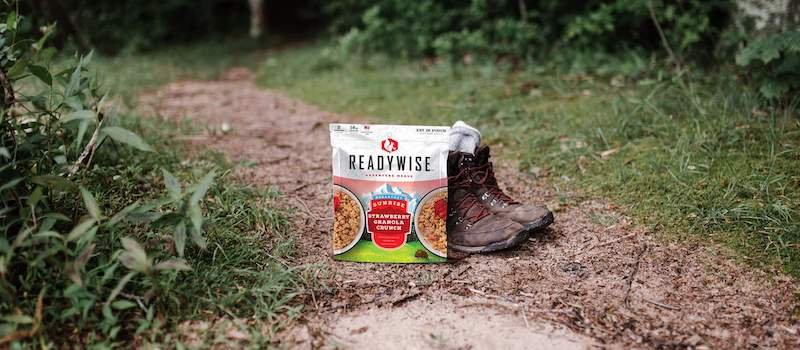 Photo of ReadyWise Strawberry Granola Crunch pack on trails next to boots