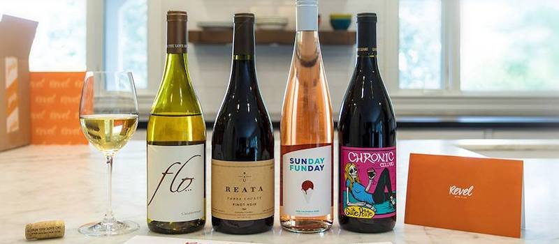 Four different wines arranged on a kitchen countertop