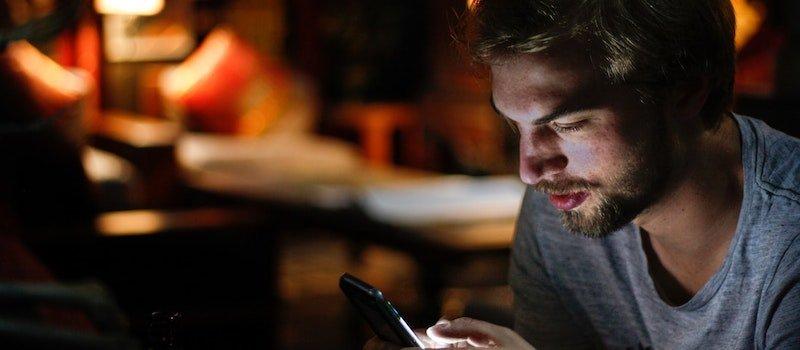 Man looking at phone screen in dark room