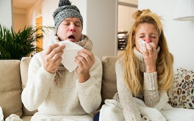Two people inside their home sneezing into tissues