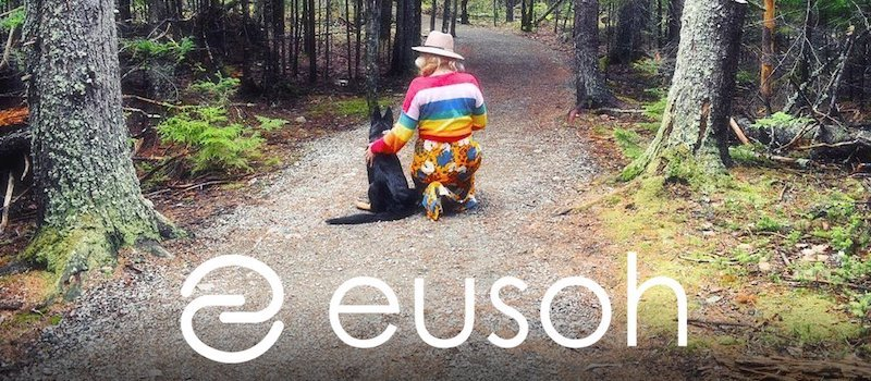 """Woman and dog on a forest trail with the word """"Eusoh"""" at the bottom of the photo"""