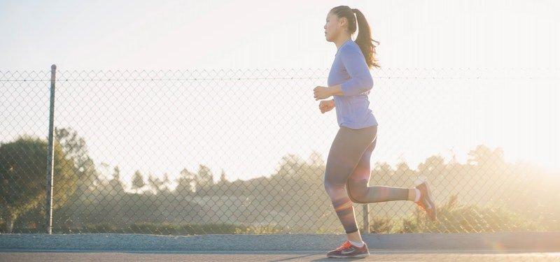 Woman running on track at sundown