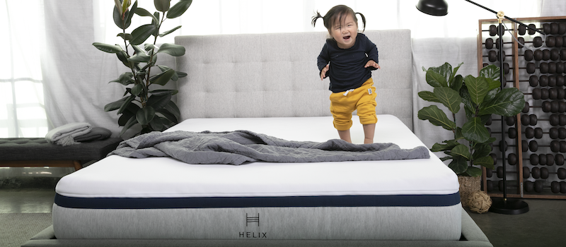 Little girl laughs and jumps on a Helix mattress