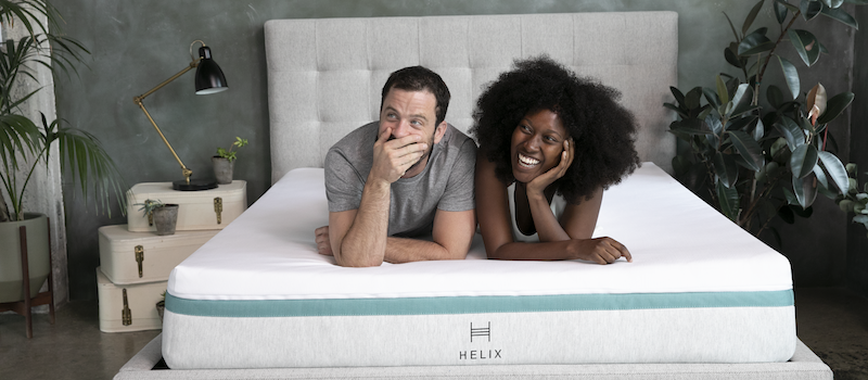 A man and woman lying down on a Helix mattress