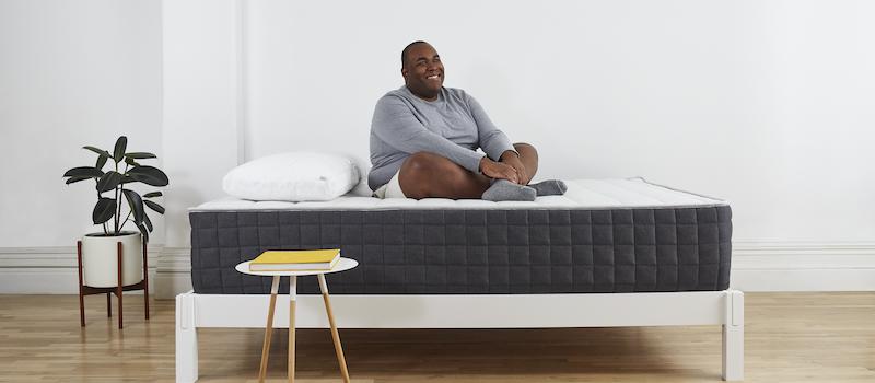 Man sits cross-legged on Helix Plus mattress