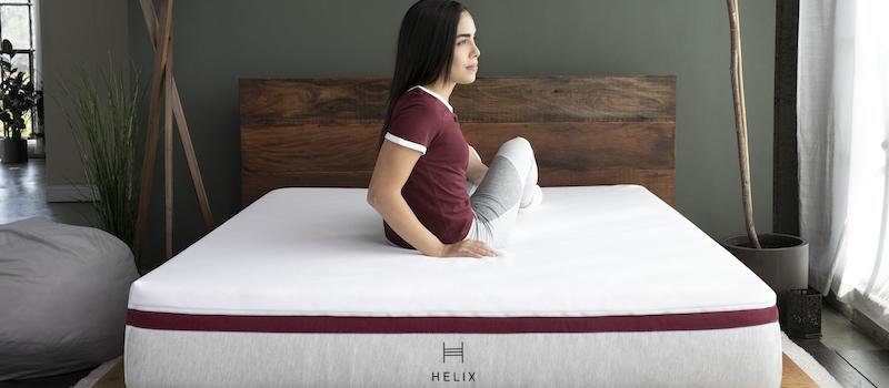Woman sits on Helix mattress