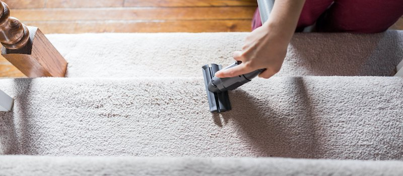 Person cleaning carpeted stairs with vacuum wand attachment