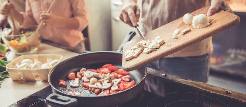 Person puts chopped mushrooms into pan