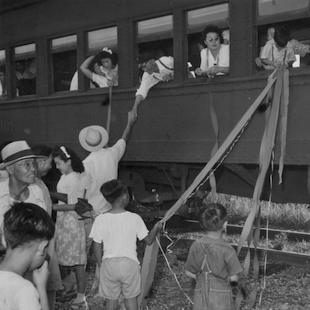 Japanese train riders holding streamers with onlookers