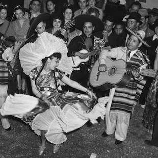 A Mexican American woman dancing to a mariachi band