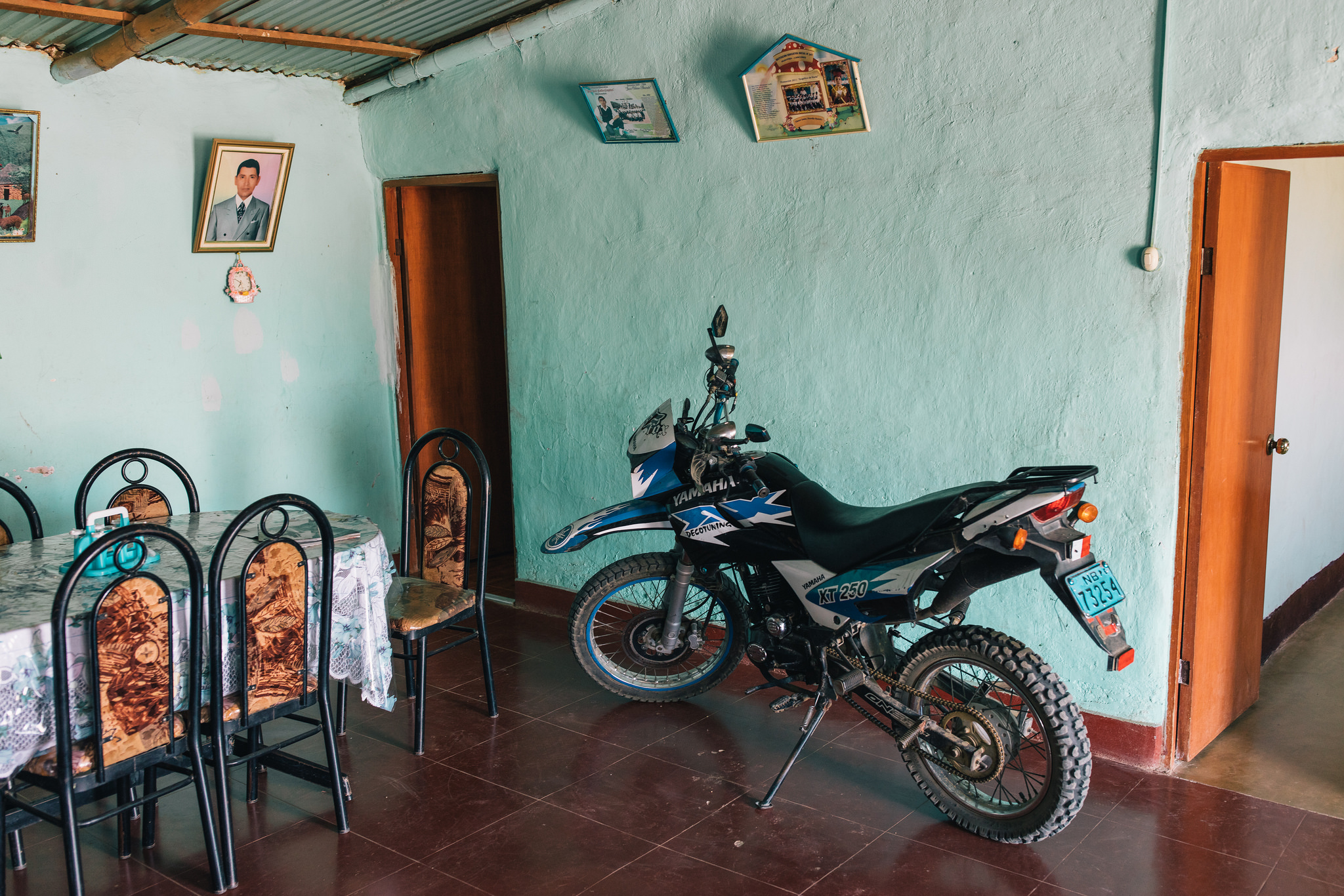 Elena's eldest son's motorcycle sits parked in the dining room, near her late husband's photo.