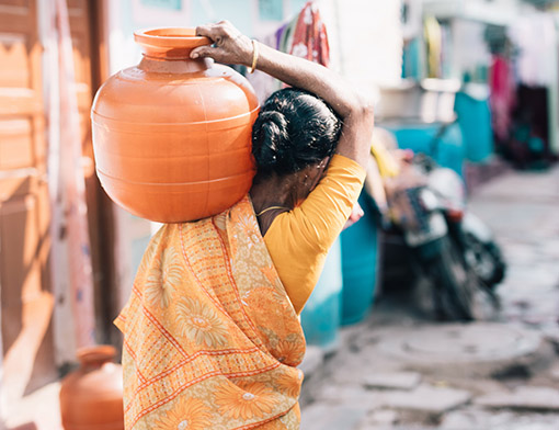 Woman carrying water in India from behind