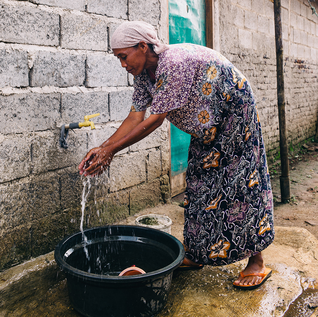 Suna, Rumyati's mother, uses their new tap.