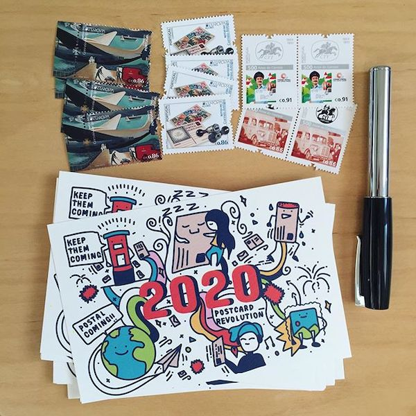 A bunch of World Postcard Day themed postcards, next to stamps and a pen