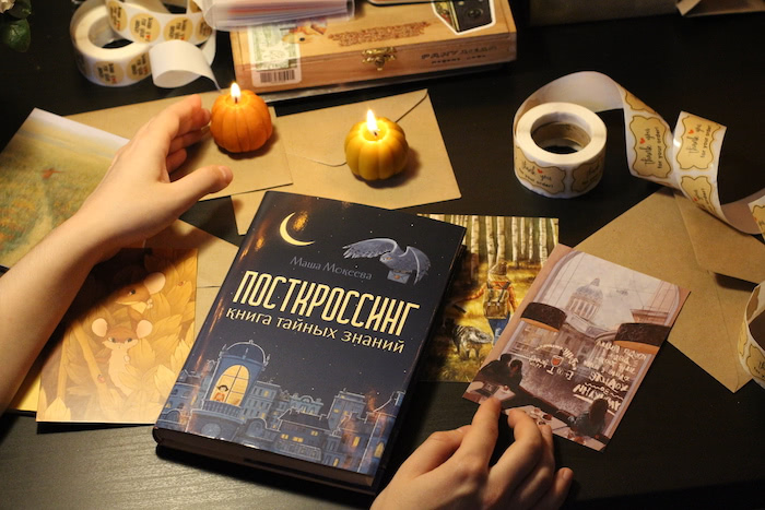 Picture of Masha's book about Postcrossing, surrounded by candles, postcards and other stationery!