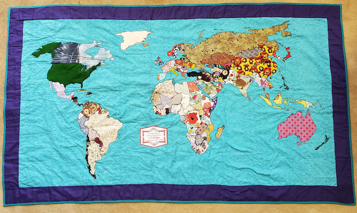A quilt featuring a world map, with different fabrics covering each country,