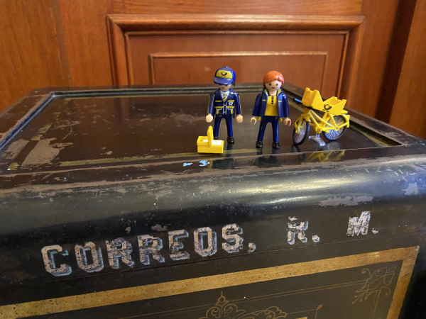 The Little Mail Carriers stand atop an old safe