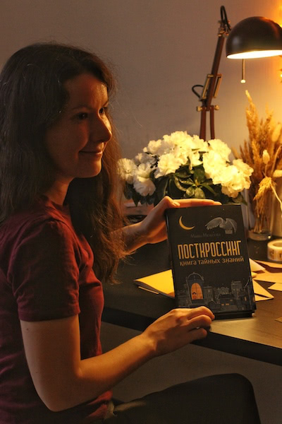 Masha holds the Postcrossing book she wrote in her hands