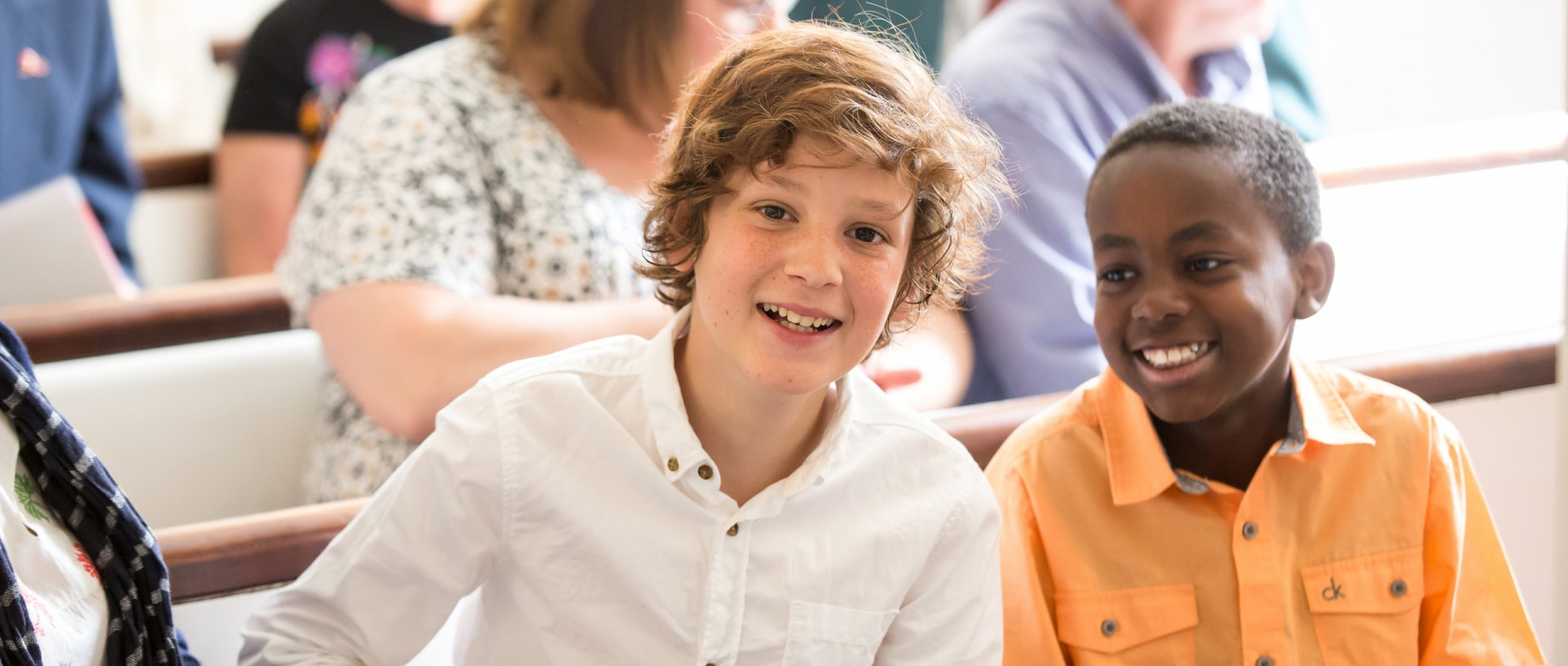 Two teenage boys smile during worship