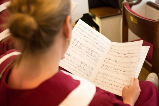 Close up shot of a woman in choir rehearsal with sheet music in her hands