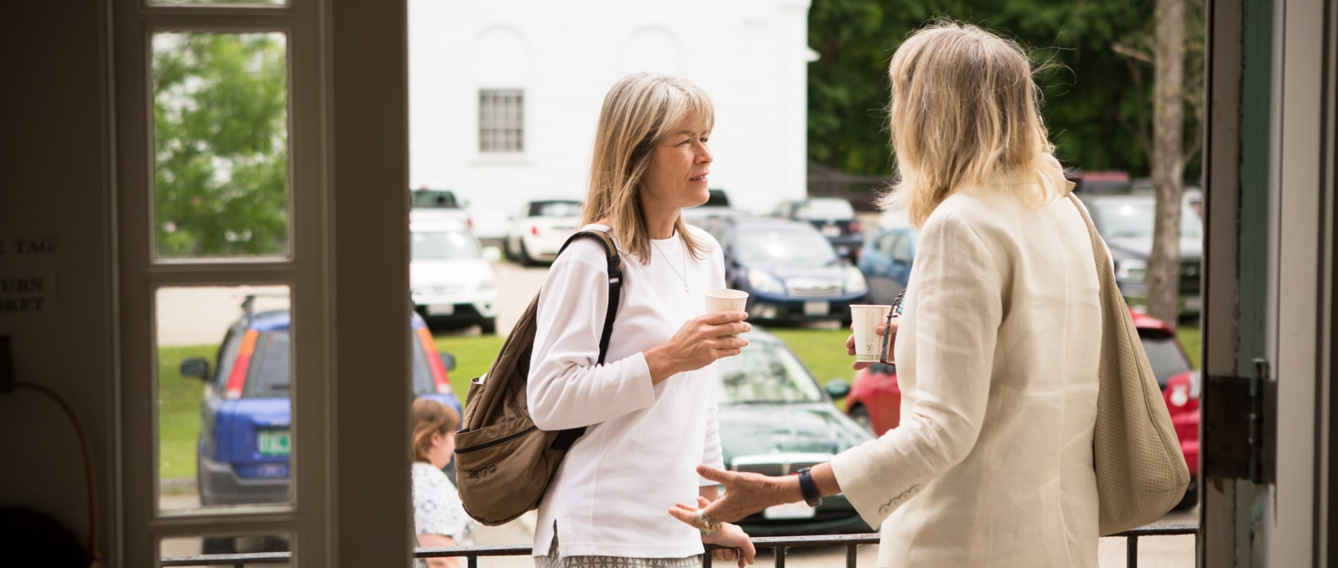 Two women drink coffee and talk at the entrance to the Stockbridge Congregational Church