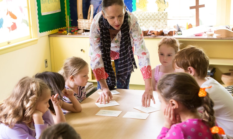 A woman teaches a Sunday School class to young children.
