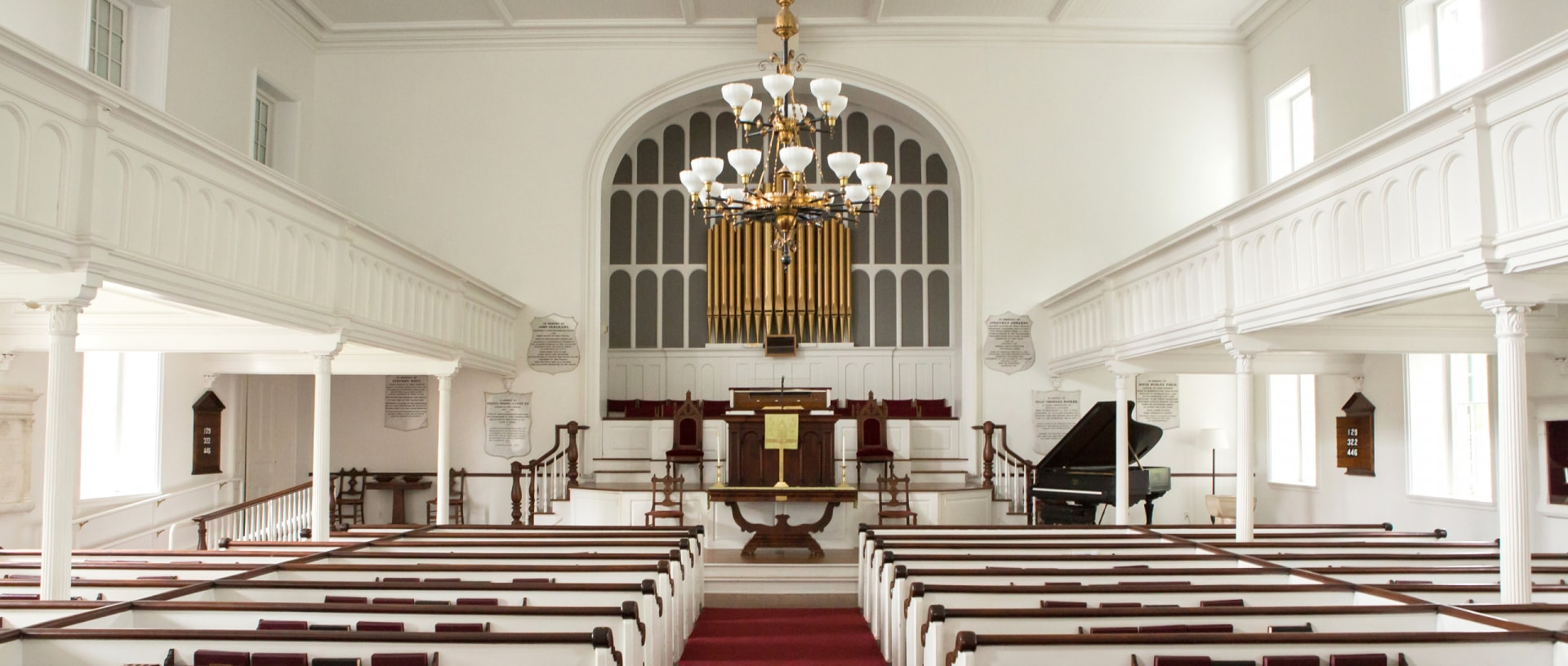 The historic sanctuary of the Stockbridge Congregational Church with white interior and red upholstry.