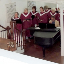 Choir members surround a piano and sing