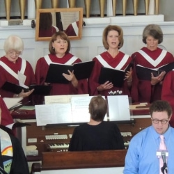 Choir members sing in front of the organ