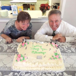 Cathy Schane-Lydon and Brent Damrow smile in front of a farewell cake