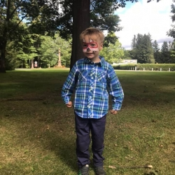A young boy with his face painted like a fox.