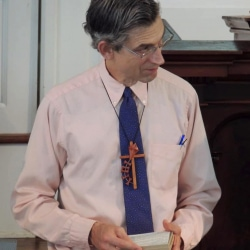 A Sunday School teacher receives a cross from the congregation in thanks for his service